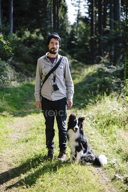 Homem com Fronteira Collie no caminho da floresta — Fotografia de Stock