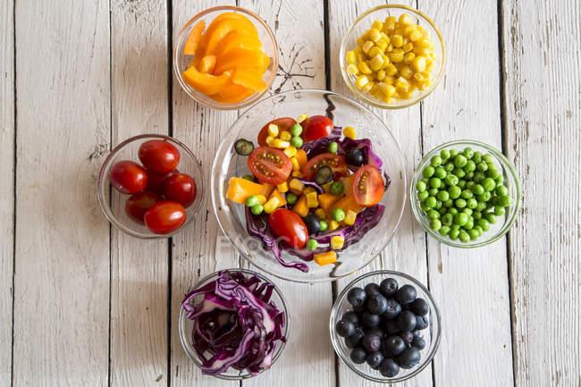 Salada mista e taças de vidro com diferentes vegetais crus de cor arco-íris dispostos em madeira branca — Fotografia de Stock