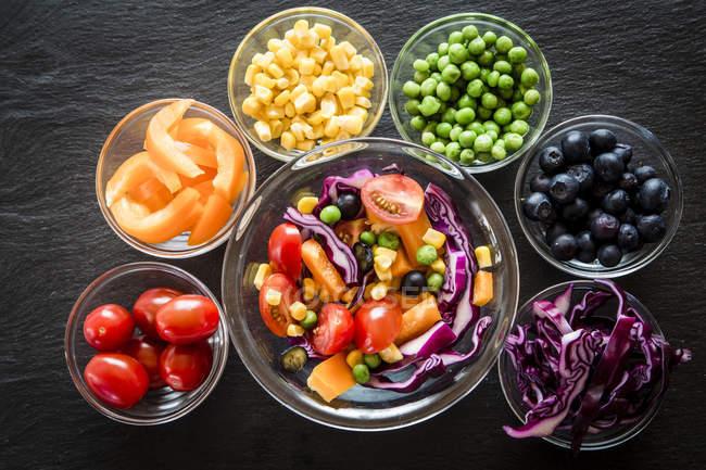 Salada mista e taças de vidro com diferentes vegetais crus dispostos em ardósia — Fotografia de Stock