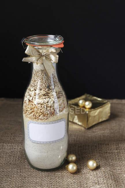 Bouteille en verre avec des ingrédients de cuisson mix pour pain de sarrasin — Photo de stock