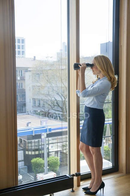 Businesswoman with binoculars looking out of window — Stock Photo