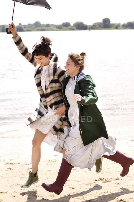 Zwei Freunde laufen Seite an Seite am Strand mit einem Sonnenschirm — Stockfoto