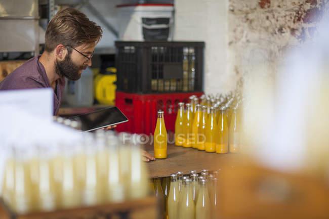 Человек с планшетом проверки запасов сока бутылки на складе — стоковое фото