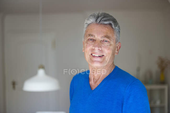 Portrait of smiling senior man at home — Stock Photo