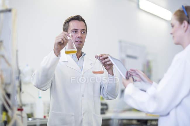 Deux scientifiques avec des liquides et une tablette numérique en laboratoire — Photo de stock