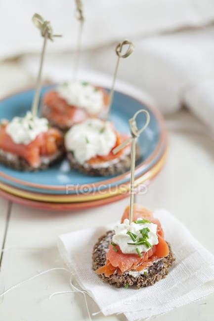 Apéritifs brochés à base de pain de seigle allemand, sauce à la crème au saumon et au raifort — Photo de stock