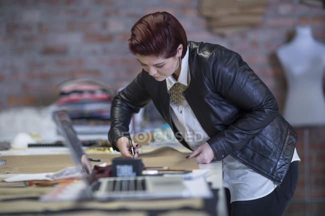 Frau schneidet Stoff auf Tisch — Stockfoto