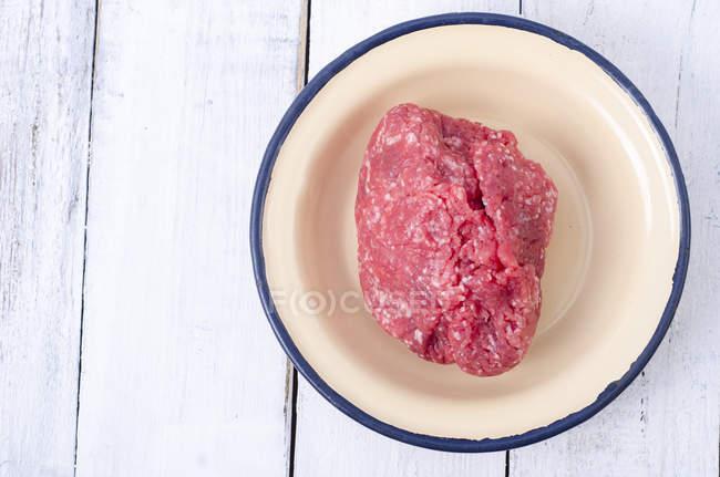 Enamel bowl of raw ground beef on white wooden table — Stock Photo