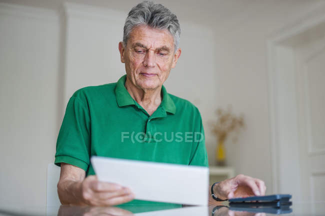 Senior man sitting at desk with paper and pocket calculator — Stock Photo