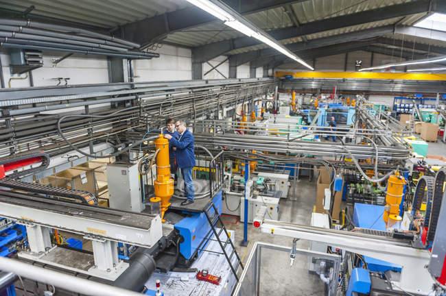 Gerente y trabajador que tiene reunión de trabajo en fábrica de plásticos - foto de stock