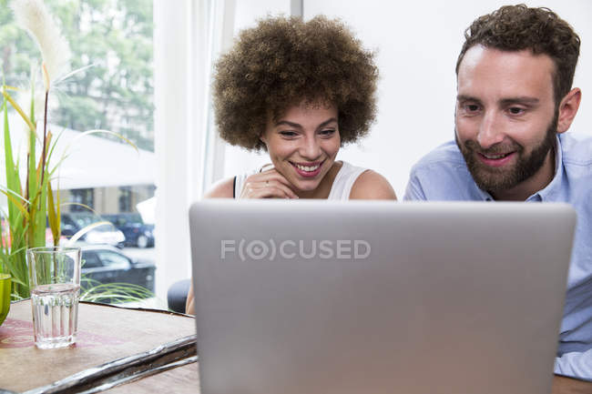 Young woman and man using laptop at the window — Stock Photo