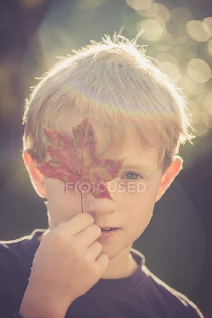 Retrato de niño cubriendo un ojo con hoja de otoño - foto de stock