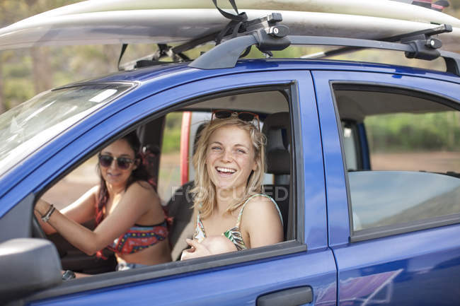 Two happy young women in car with surfboards on roof — Stock Photo
