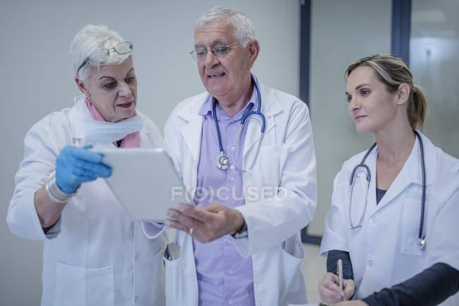 Trois médecins de discuter de la tablette numérique — Photo de stock