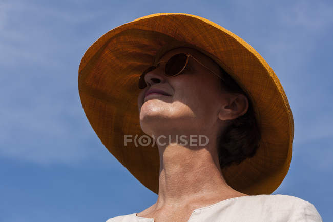 Smiling woman wearing summer hat and sunglasses — Stock Photo