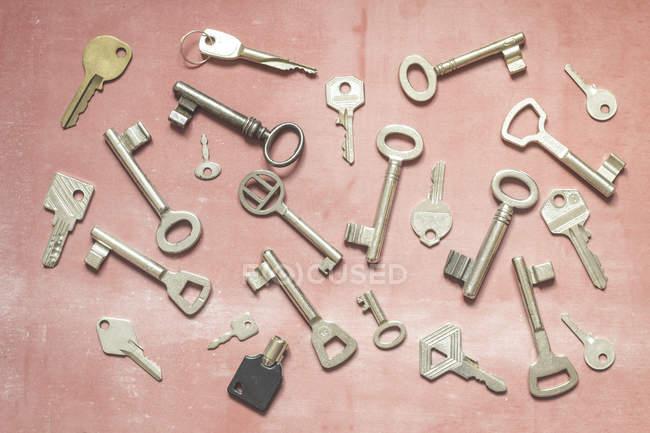 Различные ключи на розовом фоне, натюрморт — стоковое фото