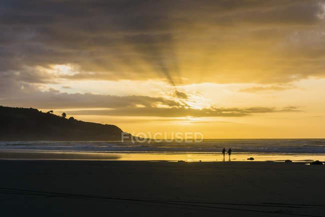 Siluetas de dos personas en la playa de retroiluminado - foto de stock