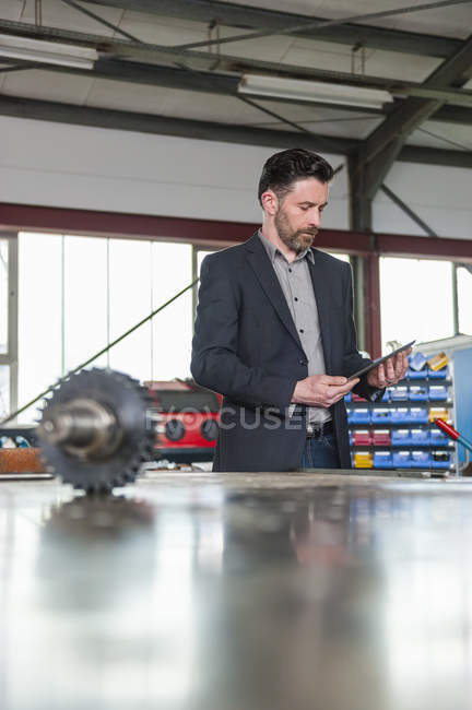 Manager with digital tablet in front of gear drive in workshop — Stock Photo