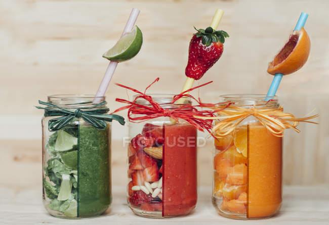 Красный, зеленый и оранжевый фруктовые коктейли в стаканах с соломинками — стоковое фото