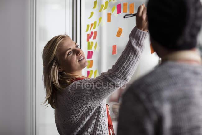 Professionnels de la création à l'aide de notes collantes au bureau — Photo de stock