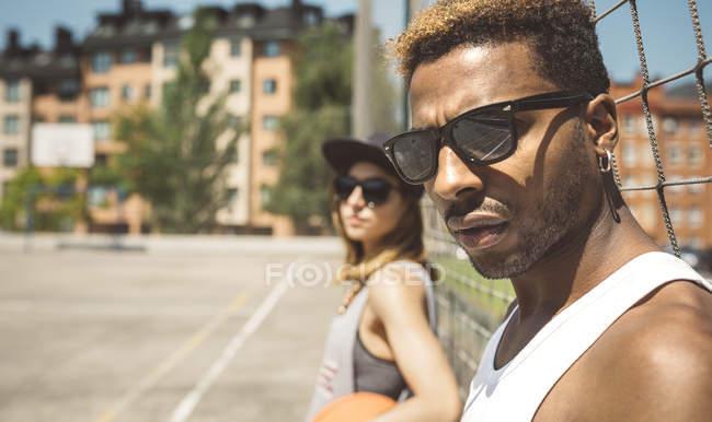 Jovem casal em pé na quadra de basquete — Fotografia de Stock