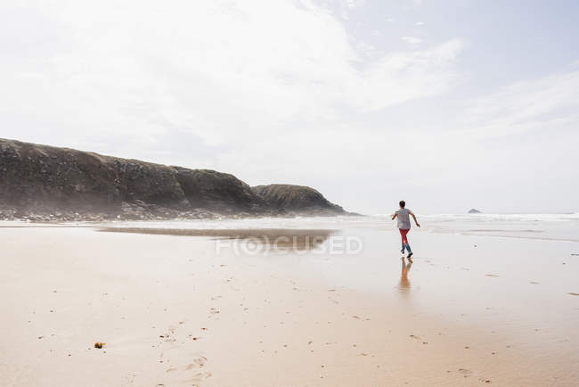 Mature woman running on the sand beach — Stock Photo