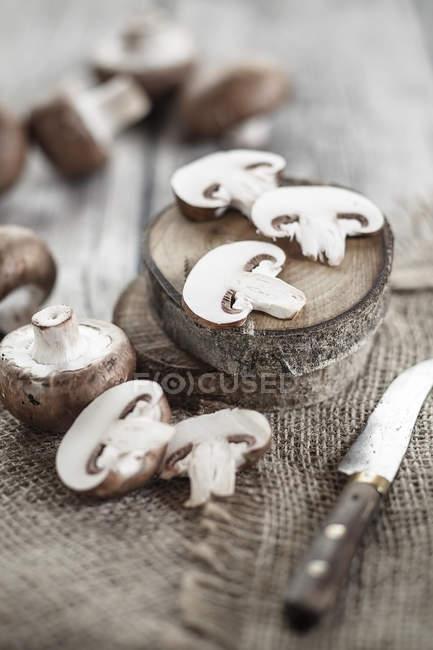 Funghi a bottone marroni affettati e interi su legno e sacco — Foto stock