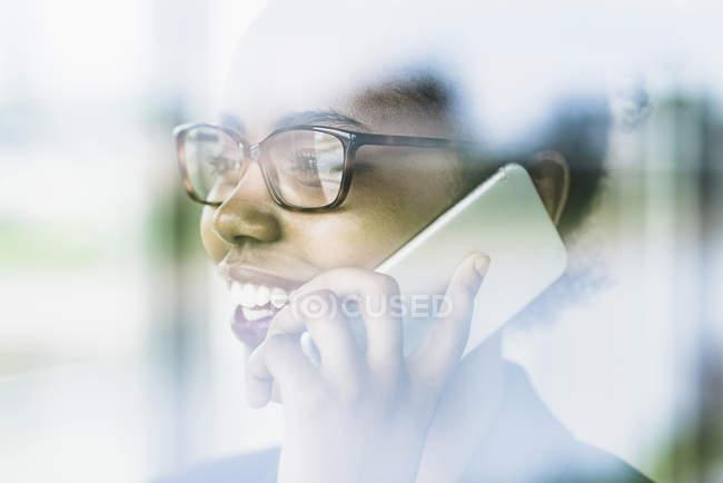 Primo piano della donna d'affari sorridente che guarda attraverso la finestra mentre telefona con lo smartphone — Foto stock