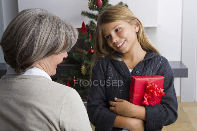 Happy girl receiving Christmas present from granny — Stock Photo