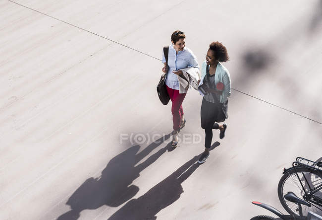 Duas mulheres de negócios andando e conversando ao ar livre — Fotografia de Stock