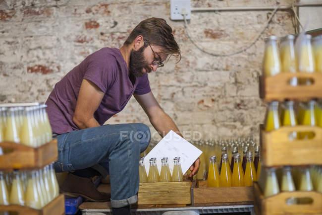 Mann überprüft Lager mit Saftflaschen, Seitenansicht — Stockfoto