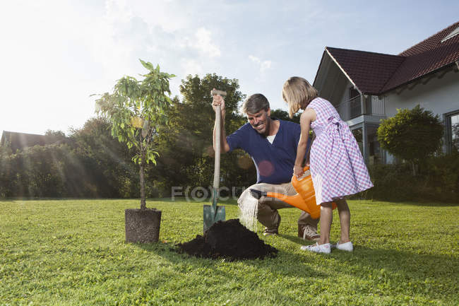 Father and daughter planting tree in garden — Stock Photo