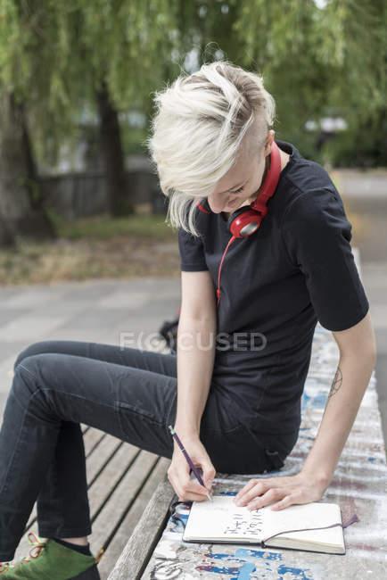 Mujer joven con auriculares dibujando en el banco del parque - foto de stock