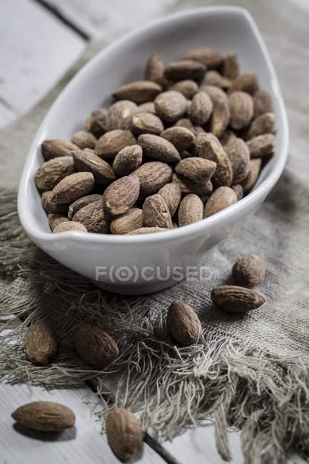 Ciotola di mandorle salate e tostate su legno con tessuto — Foto stock