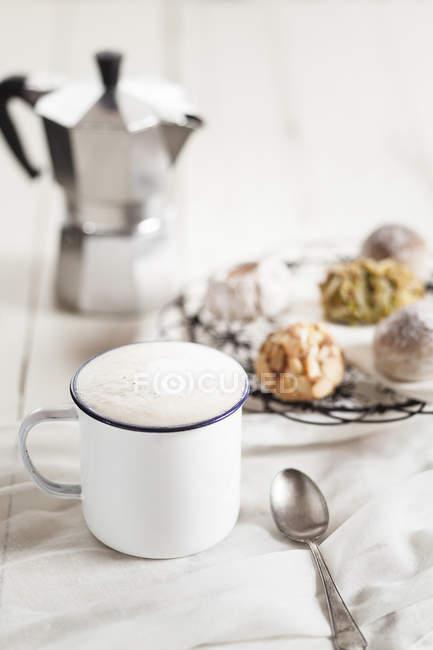 Taza de capuchino, galletas de almendras italianas y lata de espresso - foto de stock