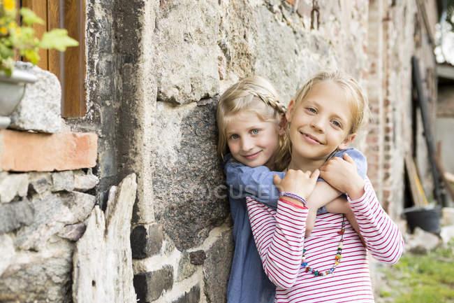Портрет двух улыбающихся девочек, прислонившихся к каменной стене — стоковое фото