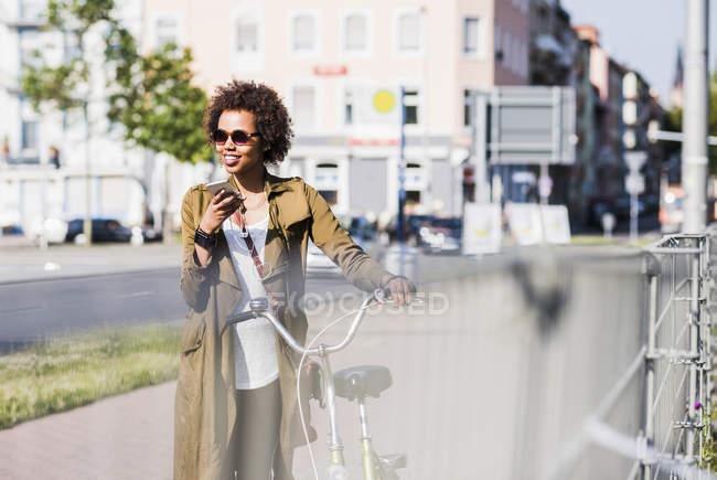 Молодая женщина со смартфоном и наушниками толкает велосипед — стоковое фото