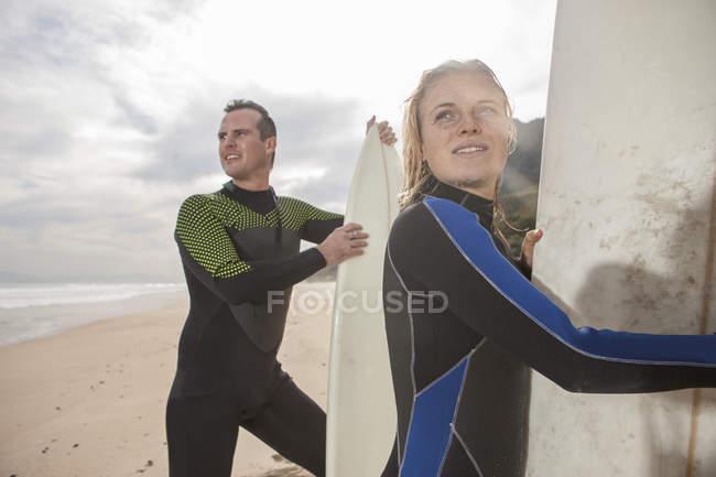 Пара с досками для серфинга на пляже, оглядывающиеся вокруг — стоковое фото