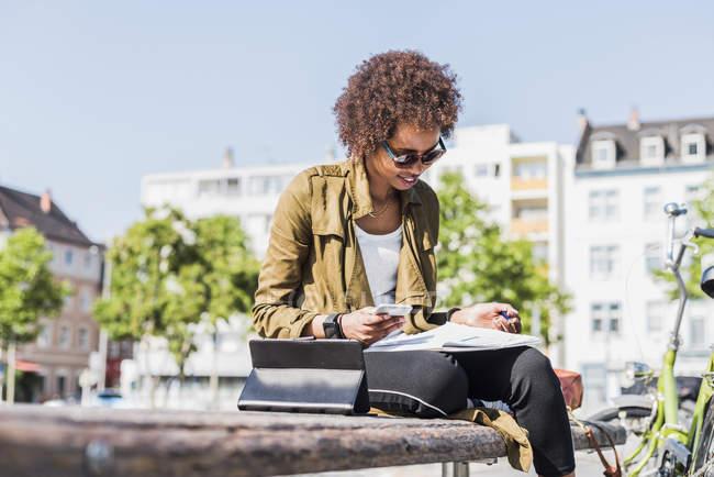 Молодая женщина сидит на скамейке и читает заметки — стоковое фото