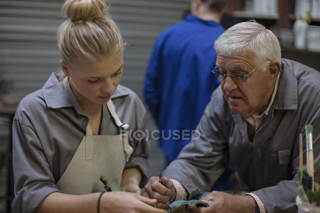 Instructor talking to trainee in workshop holding bronze cast piece — Stock Photo