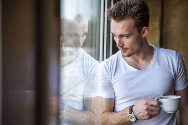Молодой человек с чашкой кофе смотрит в окно — стоковое фото