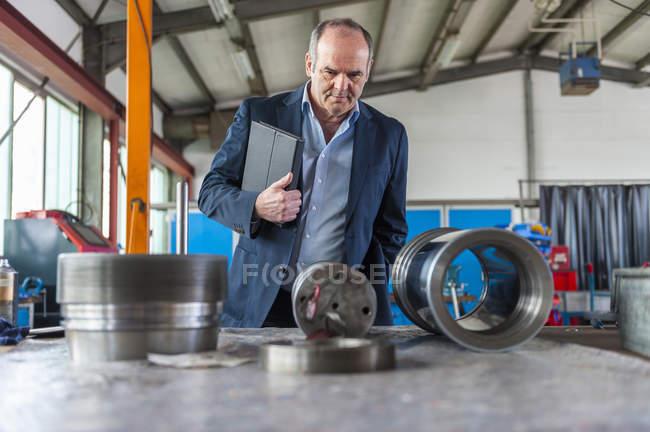Семинар, старший человек с цифровым планшетом глядя на гидравлический цилиндр — стоковое фото