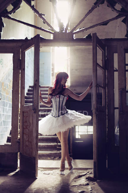 Woman with red hair and ballerina dress standing in destroyed old house at backlight — Stock Photo