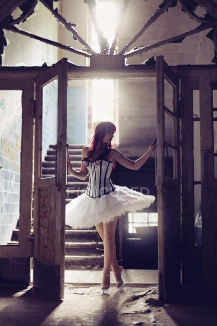 Mujer con el pelo rojo y vestido de bailarina de pie en la casa vieja destruida a la luz de fondo - foto de stock