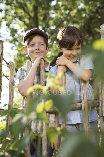 Portrait of two smiling boys standing behind a wooden fence — Stock Photo