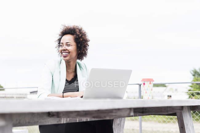 Empresária sorridente trabalhando com laptop na mesa de madeira fora — Fotografia de Stock