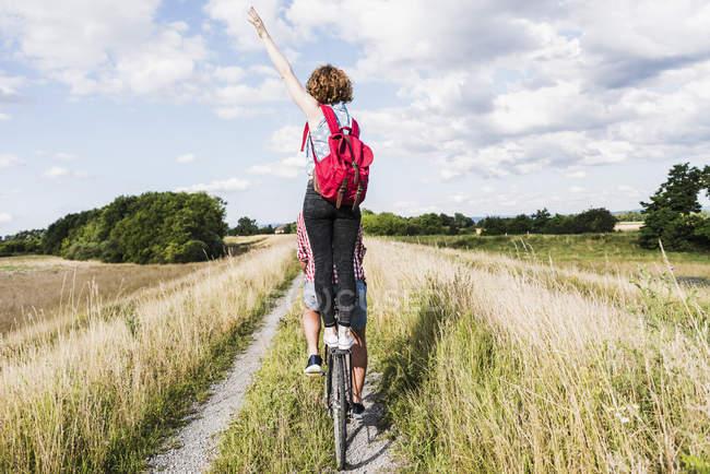 Молодая женщина, стоящая на велосипедной стойке — стоковое фото