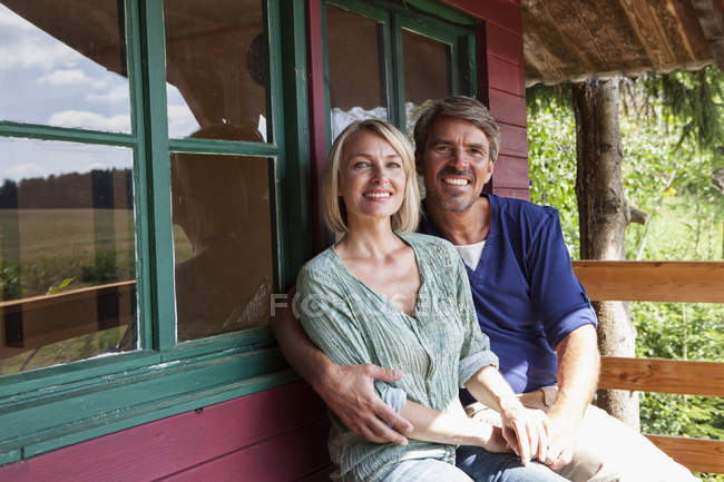 Happy mature couple on porch of summer house — Stock Photo