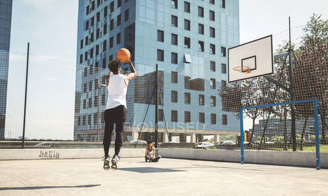 Young man aiming at basketball hoop — Stock Photo