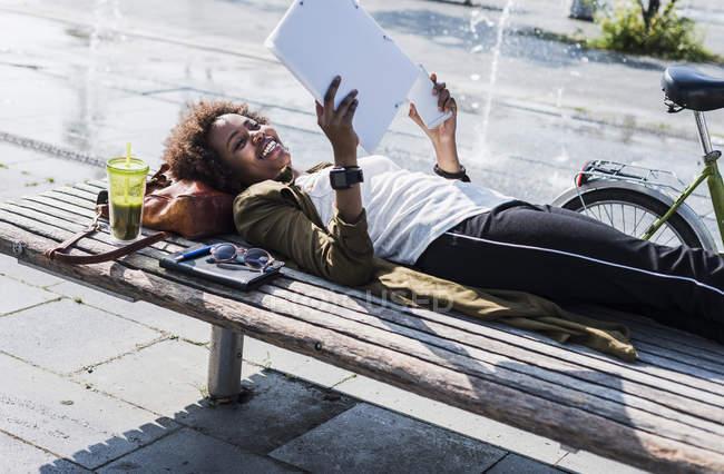 Улыбающаяся женщина лежит на скамейке и читает ноты. — стоковое фото